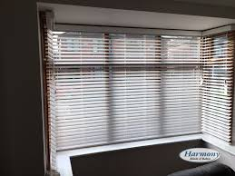 white faux wood blinds in a bay window harmony blinds of bolton