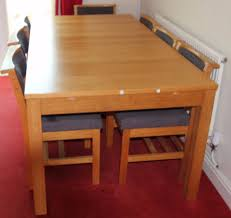 extending ikea wooden dinning table with 6 wooden chairs in