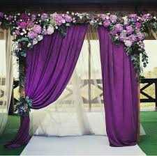picture of a wedding arch with purple curtains hydrangeas and