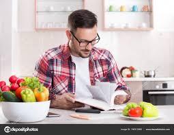 livre cuisine homme homme lisant le livre de recettes de cuisine photographie budabar
