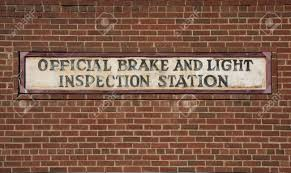brake and light inspection locations vintage brake and light inspection sign against red brick wall