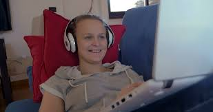 comedy film video clip steadicam shot of a laughing woman in earphones with laptop on the