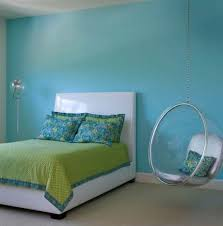 chic hanging chair with soft blue wall color and green bed sheet
