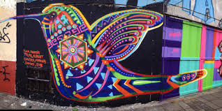 street artist guache remembers the past with his ancestral a hummingbird lends its beauty to this wall thanks to the artistic talents of street artist
