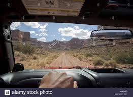 jeep utah view of remote road across red rocks through jeep window moab