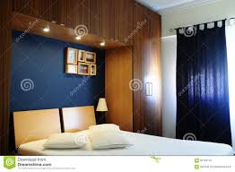 White And Dark Blue Bedroom Empty Bed Room With Dark Navy Blue Wall And Wooden Wardrobe Stock