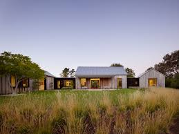 modern farm homes doors are designed to open and spill out onto a lawn modern