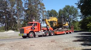 file excavator on a truck bed jpg wikimedia commons