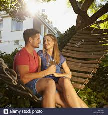 romantic young couple toasting wine while sitting on a hammock in