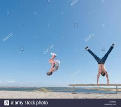 doing somersault boy doing handstand on beach bench stock
