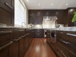 black pendant light dark wood barstools range hood green kitchen