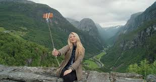 beautiful woman taking selfie photo using smartphone selfie stick