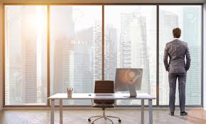Office View by Rear View Of A Ceo Of A Company Looking At Large Buildings Through