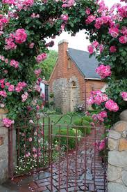 rose covered arch over a metal gate leading to a lovely old garden