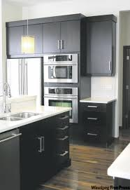 black kitchen cabinets with white countertops dark expresso cabinets topped with white quartz countertops create