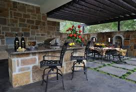 traditional outdoor kitchen design with high brick fireplace and
