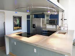 grey island with concrete countertop blue cabinets side by side