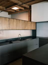 kitchen with grey cupboards black bench top and wooden detail san