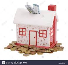 house shaped piggy bank with euro coins and notes stock photo