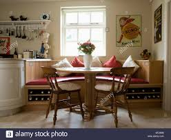 circular table and old wooden chairs in kitchen dining room with circular table and old wooden chairs in kitchen dining room with fitted banquette seating