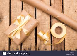 brown paper wrapping present lying on wooden surface with golden