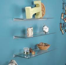 decorating clear glass floating shelves on aqua blue wall