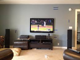 rectangle black led tv on grey wall with black speaker and dark