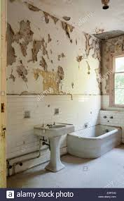 old bathroom with torn peeling wallpaper white wall tiling and