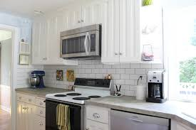 white kitchen backsplash white kitchen cabinets grey countertops kitchen subway tile backsplash in a traditional kitchen design