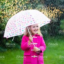 little with umbrella in rainy summer park stock photo