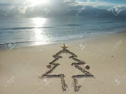 christmas tree drawn in sand at the beach holiday concept stock