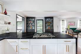 white kitchen cabinets with gold countertops black quartz waterfall countertop in a black and white