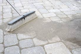 broom sweeping locking sand into backyard patio pavers stock photo