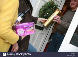 guests arrive at the front door of a house carrying gifts for a