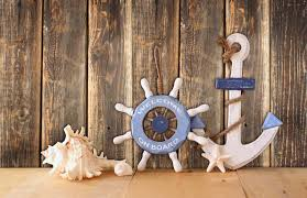 nautical wood wheel anchor and shells on wooden table