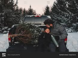 father and daughter on back of pick up truck with their christmas