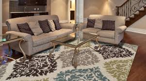 floral area rug for living room design with pinstripe sofas and a