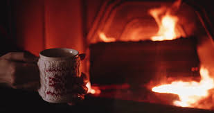 woman hands holding coffee or tea cup against cozy fireplace in