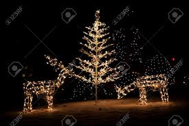 lighted reindeer and christmas tree yard art in the snow stock