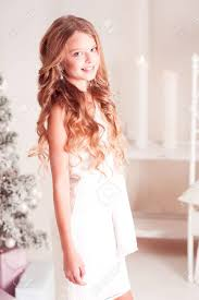 long hair on 66 year old cheerful teen girl 14 15 year old wearing white dress in room