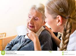 Home Nurse by Nurse Wiping Mouth Of Senior Woman In Nursing Home Stock Photo