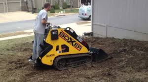 using a boxer mini excavator to grade a drainage swale in a