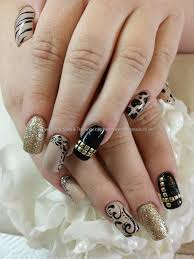 black and gold freehand nail art over acrylic nails nails
