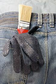 working gloves and brush in the back pocket of old used jeans