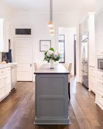 gray kitchen island upholstered counter stools flank a slim gray kitchen island