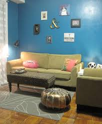 green sofa and pink cushions in small blue paint wall of living