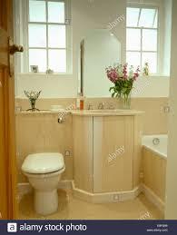 modern bathroom toilet beside basin in vanity unit with pale wood