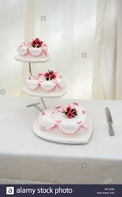 heart shaped wedding cakes three tier heart shaped wedding cake and knife on a table stock