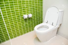 clean white toilet and paper rolls with lime green mosaic tiles