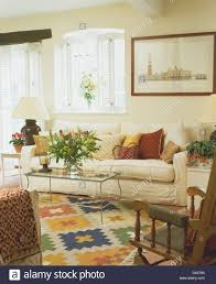 white plantation shutters on window above cream sofa in cottage